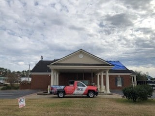 Recent home remodeling work (roofing) done on a home in Georgia damaged by Hurricane Michael. It's a commercial building. A blue tarp is covering a portion of the roof & a roofer is on the very top of the roof.