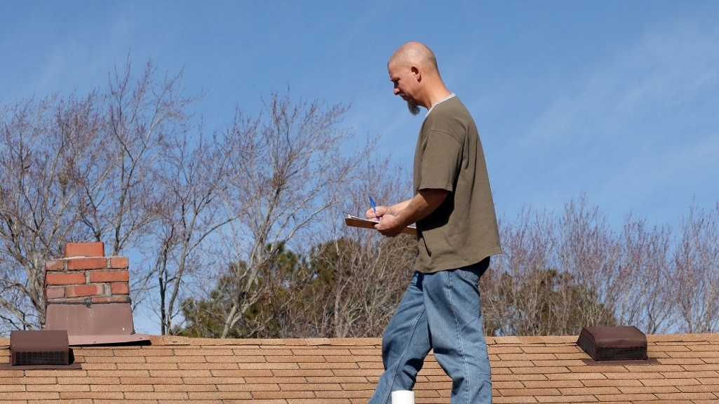 Check roof when buying home image shows man on top of roof. He has a clipboard in his hand & is writing down information.