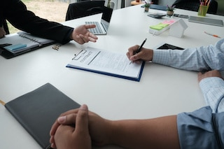 customer reviewing proposal contract with roofing contractor