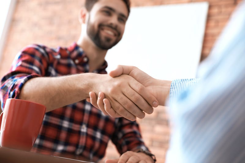 roofing contractor shaking hands with client after interview