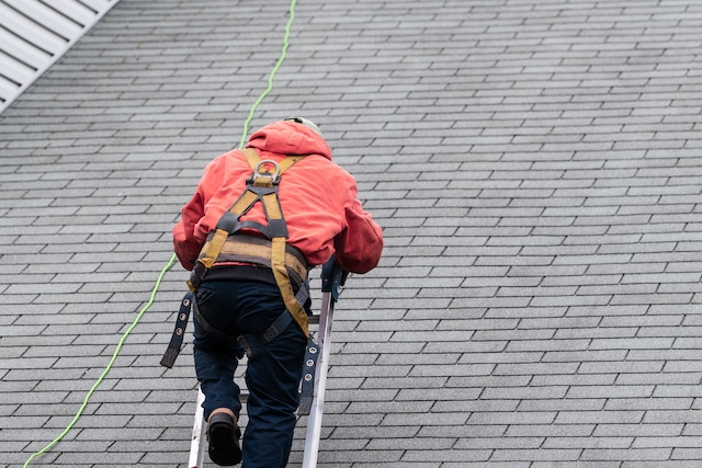 roof inspection expert climbing up latter to roof top
