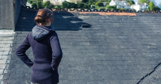 woman checks her roof with checklist signs you need a new roof