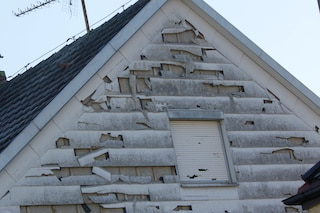 hail damaged vinyl siding with many holes needs siding repairs or replacement