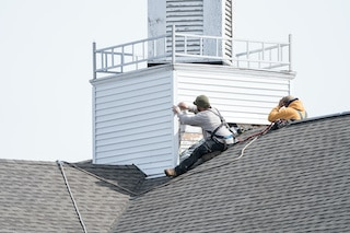 wood siding repairs with two contractors on roof of church