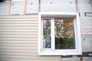 installation of siding on side of house with window