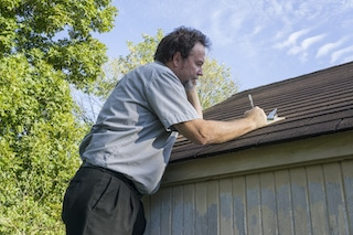 man looking at checklist when doing roofing maintenance inspection