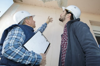 contractor and foreman discuss cracked ceilings and roof repairs