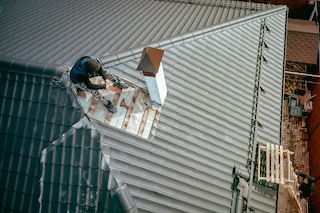 roof repair contractor resting on top of roof near chimney