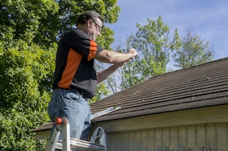 roofing contractor takes pictures of hail damage to roof for insurance claim