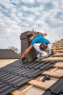 ace roofing contractor works around chimney in metal roof installation over wood underlayment