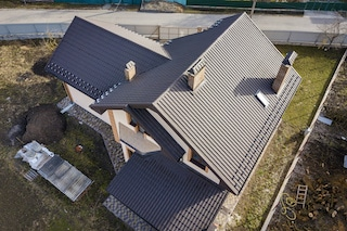 metal roof installation of tiles on new home by ace construction and remodeling